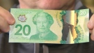 Michael Boddy holds up a fake $20 bill. He says he unwittingly received 63 of the counterfeit banknotes in exchange for a high-end iPhone.