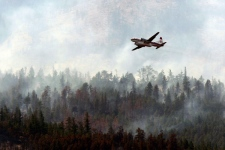 A water bomber flies past a wildfire burning out of control in Kelowna, B.C., on Monday July 20, 2009. (Darryl Dyck / THE CANADIAN PRESS)