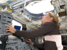 Canadian Space Agency astronaut Julie Payette, STS-127 mission specialist, looks through an overhead window while operating controls on the aft flight deck of space shuttle Endeavour during flight day two activities. (NASA)