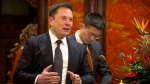 In this Jan. 9, 2019, file photo, Tesla CEO Elon Musk speaks during a meeting with Chinese Premier Li Keqiang at the Zhongnanhai leadership compound in Beijing. Electric car and solar panel maker Tesla said Friday, Jan. 18, 2019 it plans to cut its staff by about 7 percent. (AP Photo/Mark Schiefelbein, Pool, File)