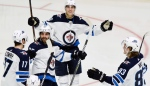 Winnipeg Jets left wing Brandon Tanev, top, celebrates with teammates after scoring a goal against the Nashville Predators during the third period of an NHL hockey game Thursday, Jan. 17, 2019, in Nashville, Tenn. The Jets won 5-1. (Source: AP Photo/Mark Zaleski)