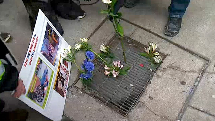 Advocates for the city's homeless place flowers on a grate near to where a homeless woman was struck and killed by a garbage truck as she lay asleep in a laneway.