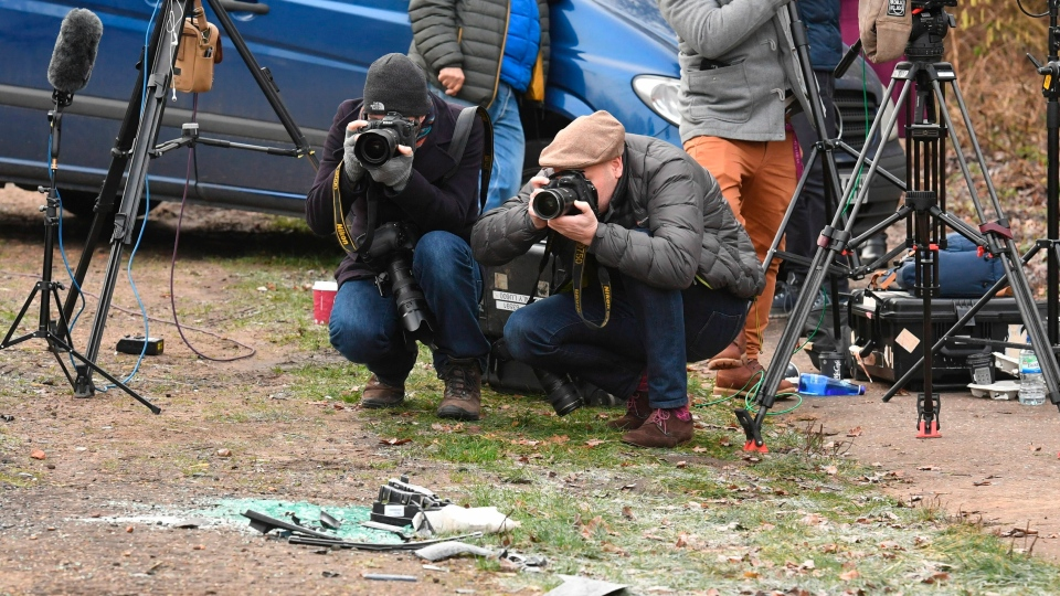 News media film broken glass and car parts on the road side near to the Sandringham Estate, England, where Prince Philip was involved in a road accident Thursday while he was driving, Friday Jan. 18, 2019.  (John Stillwell/PA via AP)