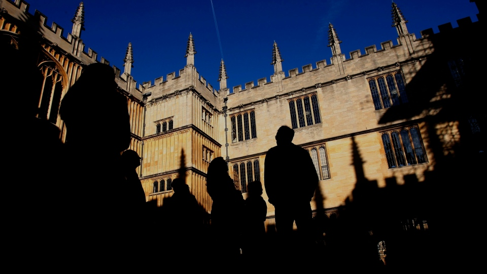People are silhouetted in the Old Schools Quadrangle, Old Bodleian Library first opened to scholars in 1602 at Oxford University in Oxford, England, Friday, Oct. 17, 2008. (AP Photo/Kirsty Wigglesworth)