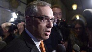 Tony Clement fields questions in the foyer outside the House of Commons in Ottawa, Monday, May 11, 2015. THE CANADIAN PRESS/Adrian Wyld