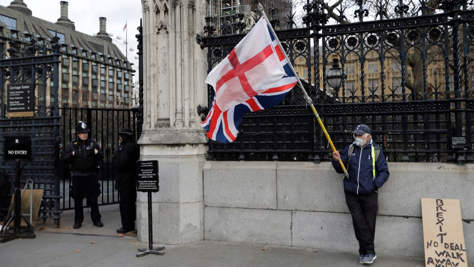 A lone demonstrator stands by an entrance to Britain's parliament in London, Friday, Jan. 18, 2019. (AP Photo/Kirsty Wigglesworth)