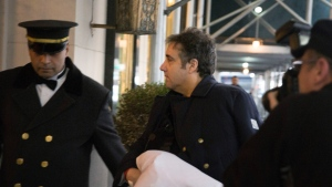 Michael Cohen arrives at his home in New York with his left arm in a sling supported by a pillow Friday, Jan. 18, 2019. (AP Photo/Kevin Hagen)