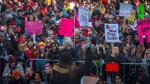 People listen to a speaker as they gather in Nathan Phillips Square, before embarking on a Women's March in Toronto on Saturday, January 20, 2018. THE CANADIAN PRESS/Chris Young