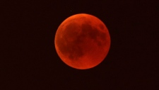 A blood moon rises over Marseille, southern France, Friday, July 27, 2018. Curiosity and awe have greeted a complete lunar eclipse, the longest one of this century. (AP Photo/Claude Paris)
