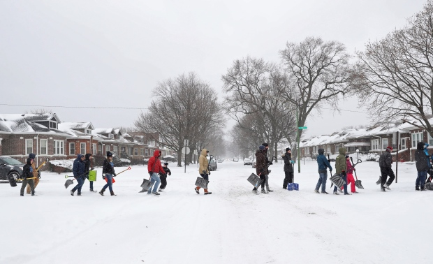 Volunteers walk along South Wabash Avenue to start shoveling snow in the Chatham neighborhood Saturday, Jan. 19, 2019, in Chicago. Organized by My Block, My Hood, My City, more than 50 people gathered to clear snow from sidewalks and front steps throughout the South Side. (John J. Kim/Chicago Tribune via AP)