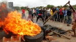 In this Tuesday, Jan. 15, 2019 file photo, protestors gather near a burning tire during a demonstration over the hike in fuel prices in Harare, Zimbabwe. (AP Photo/Tsvangirayi Mukwazhi, File)