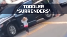 Toddler raises her hands as parents arrested