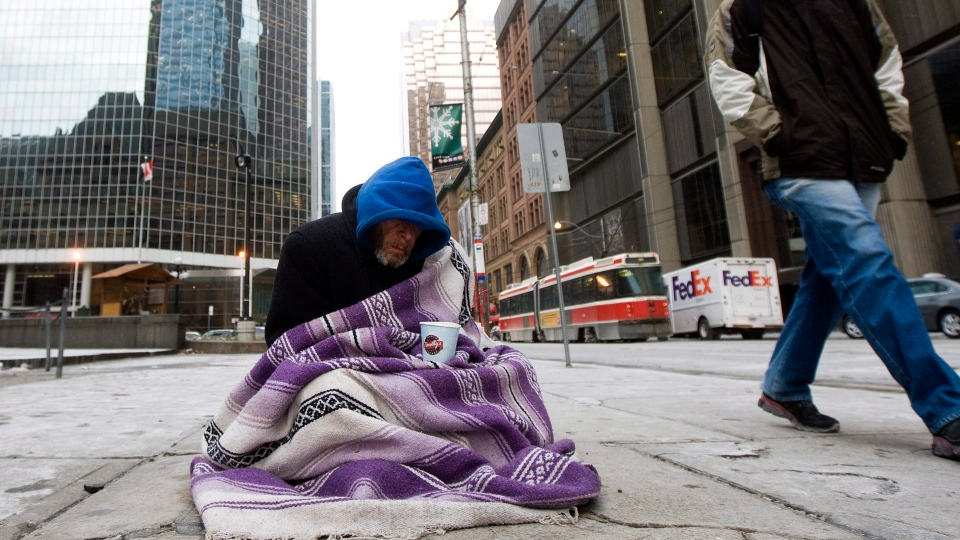 In this file photo, a homeless person panhandles for money during an extreme cold weather alert for the City of Toronto on Monday, December 13, 2010. THE CANADIAN PRESS/Nathan Denette
