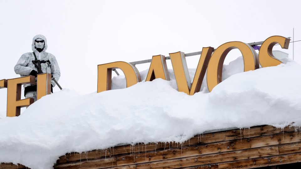 An armed Swiss police officer stands guard on the roof of a hotel near the congress center where the annual meeting of the World Economic Forum, WEF, take place in in Davos, Monday, Jan. 21, 2019. (AP Photo/Markus Schreiber)
