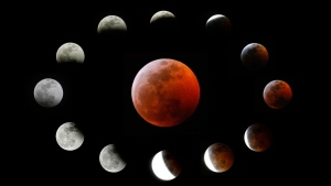 This combination photo shows the totally eclipsed moon, center, and others at the different stages during a total lunar eclipse, as seen from Los Angeles, Sunday, Jan. 20, 2019. (AP Photo/Ringo H.W. Chiu)