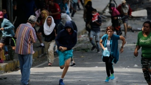 Anti-government protesters run during clashes with security forces as they show support for an apparent mutiny by a national guard unit in the Cotiza neighborhood of Caracas, Venezuela, Monday, Jan. 21, 2019. (AP Photo/Ariana Cubillos)