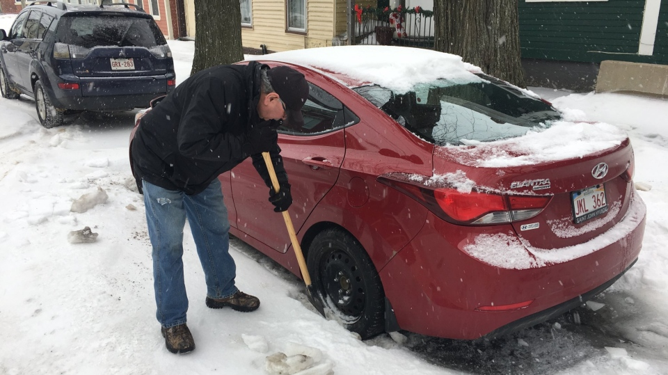 A Saint John resident chips away at the ice and snow that coated his car following a messy storm on Jan. 21, 2019.