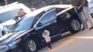 Little girl puts hands up, mimicking parents under