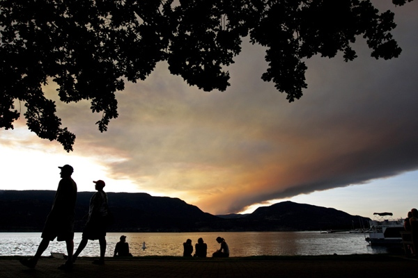 Smoke from wildfires rises and hangs in the air at sunset as people walk along Lake Okanagan in Kelowna, B.C., on Sunday July 19, 2009. (Darryl Dyck / THE CANADIAN PRESS)