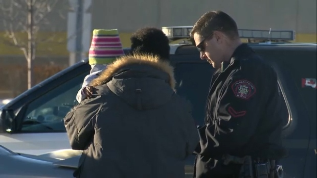 A CPS member speaks with a man who was reunited with his infant child on Monday afternoon after the family's car was stolen with the child inside from a location near Sunridge Mall