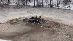 Both managed to get out of a submerged vehicle after she slid off the road and into an icy pond.