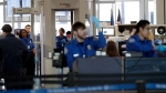 FILE- In this Jan. 5, 2019, file photo Transportation Security Administration officers work at a checkpoint at O'Hare airport in Chicago.  (AP Photo/Nam Y. Huh, File)