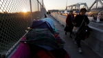 In this Thursday, Jan. 10, 2019, photo pedestrians pass a makeshift encampment where migrants seeking asylum wait in Matamoros, Mexico, on a bridge connecting the U.S. and Mexico. (AP Photo/Eric Gay)