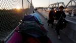 In this Thursday, Jan. 10, 2019, photo pedestrians pass a makeshift encampment where migrants seeking asylum wait in Matamoros, Mexico, on a bridge connecting the U.S. and Mexico. (AP Photo/Eric Gay)