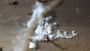 In this Dec. 21, 2018 file handout photo provided a Sudanese activist, a protester stands in tear gas during clashes with security forces in Khartoum, Sudan. (Sudanese Activist via AP, File)