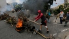 Anti-government protesters create burning roadblocks during clashes with security forces, as they show support for a mutiny by a National Guard unit in the Cotiza neighborhood of Caracas, Venezuela, Monday, Jan. 21, 2019. Venezuela's government said Monday it put down the mutiny. (AP Photo/Fernando Llano)