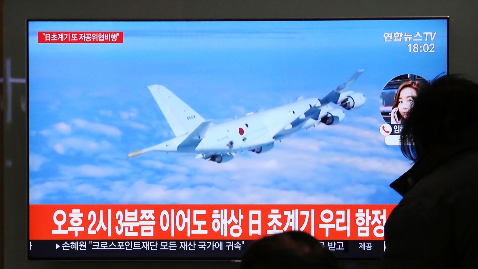 People watch a TV screen showing file footage of a Japanese patrol plane during a news program at the Seoul Railway Station in Seoul, South Korea, Wednesday, Jan. 23, 2019. (AP Photo/Ahn Young-joon)