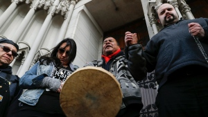 Native American protesters hold hands with parishioner Nathanial Hall, right, during a group prayer outside the Catholic Diocese of Covington Tuesday, Jan. 22, 2019, in Covington, Ky. (AP Photo/John Minchillo)
