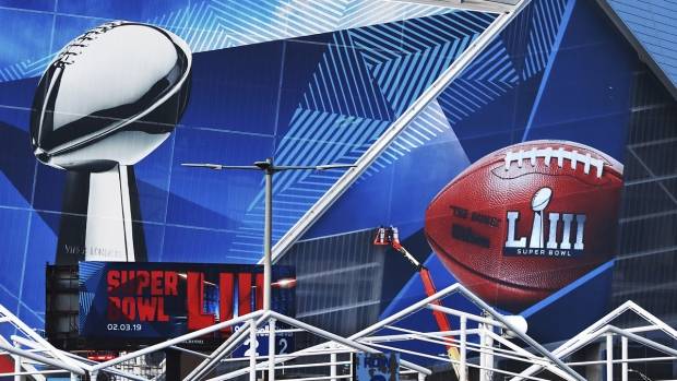 Workers use a lift to install a Super Bowl 53 wrap on the outside of Mercedes-Benz Stadium  in Atlanta, on Jan. 17, 2019. (Curtis Compton / Atlanta Journal-Constitution via AP)