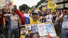 An opposition member holds a poster board with the prices of basic food during a protest against Venezuela's President Nicolas Maduro in Caracas, Venezuela, Wednesday, Jan. 23, 2019. Venezuela's re-invigorated opposition faces a crucial test Wednesday as it seeks to fill streets nationwide with protesters in an appeal to the military and the poor to shift loyalties that until recently looked solidly behind Maduro's government. (AP Photo/Fernando Llano)