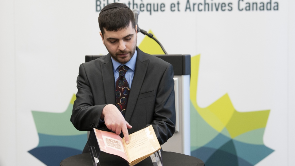 "Michael Kent, curator of the Jacob M. Lowy collection, displays the German language book ""Statistics, Media and Organizations of Jewry in the United States and Canada,"" Wednesday January 23, 2019 in Ottawa. The book, once owned by Adolf Hitler, has been acquired by Library and Archives Canada. THE CANADIAN PRESS/Adrian Wyld"