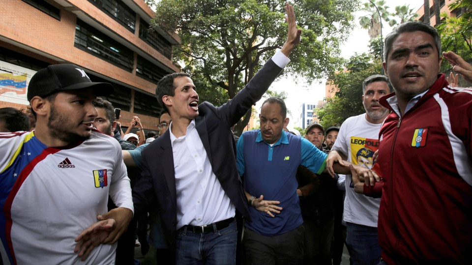 Juan Guaido waves at supporters after declaring himself interim president of the South American country, during a rally demanding the resignation of President Nicolas Maduro, in Caracas, Venezuela, Wednesday, Jan. 23, 2019. (AP / Boris Vergara)