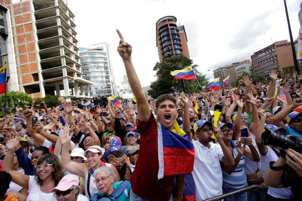 Anti-government protesters cheer after Juan Guaido, head of Venezuela's opposition-run congress, declares himself interim president of the South American country until a new election can be called, at a rally demanding the resignation of President Nicolas Maduro, in Caracas, Venezuela, Wednesday, Jan. 23, 2019. (AP Photo/Boris Vergara)
