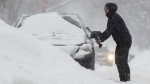A woman clears snow from her car in Ottawa on Wednesday January 23, 2019. Up to 30cm of snow is forecast to fall in the region followed by freezing rain. THE CANADIAN PRESS/Adrian Wyld