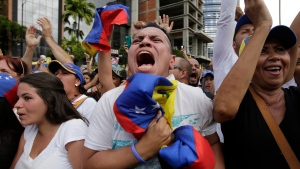 Anti-government protesters cheer as Juan Guaido, head of Venezuela's opposition-run congress, declares himself interim president of the South American country until a new election can be called, at a rally demanding the resignation of President Nicolas Maduro in Caracas, Venezuela, Wednesday, Jan. 23, 2019. (AP / Boris Vergara)