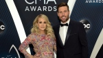 In this Nov. 14, 2018 file photo, Carrie Underwood and her husband Mike Fisher arrive at the 52nd annual CMA Awards in Nashville, Tenn. (Photo by Evan Agostini/Invision/AP, File)