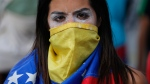 An anti-government protester wears a Venezuelan flag to cover her face, after a rally demanding the resignation of President Nicolas Maduro in Caracas, Venezuela, Wednesday, Jan. 23, 2019. (AP / Fernando Llano)