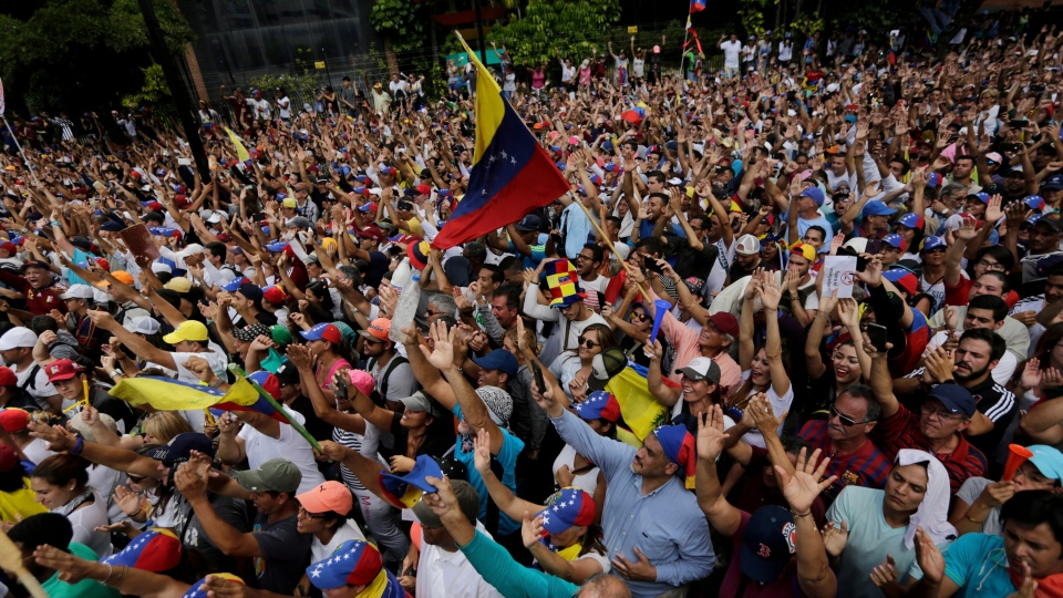Anti-government protesters hold their hands up during the symbolic swearing-in of Juan Guaido, head of the opposition-run congress who declared himself interim president of Venezuela until elections can be called, during a rally demanding President Nicolas Maduro's resignation in Caracas, Venezuela, Wednesday, Jan. 23, 2019. (AP Photo/Fernando Llano)