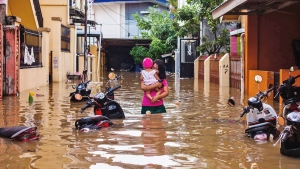 A woman carries her daughter as she wades through a flooded neighborhood in Makassar, South Sulawesi, Indonesia, Wednesday, Jan. 23, 2019. (AP Photo/Yusuf Wahil)
