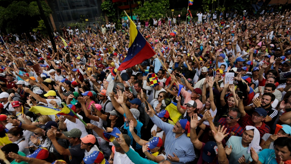 Anti-government protesters hold their hands up during the symbolic swearing-in of Juan Guaido, head of the opposition-run congress who declared himself interim president of Venezuela until elections can be called, during a rally demanding President Nicolas Maduro's resignation in Caracas, Venezuela, Wednesday, Jan. 23, 2019. (AP / Fernando Llano)