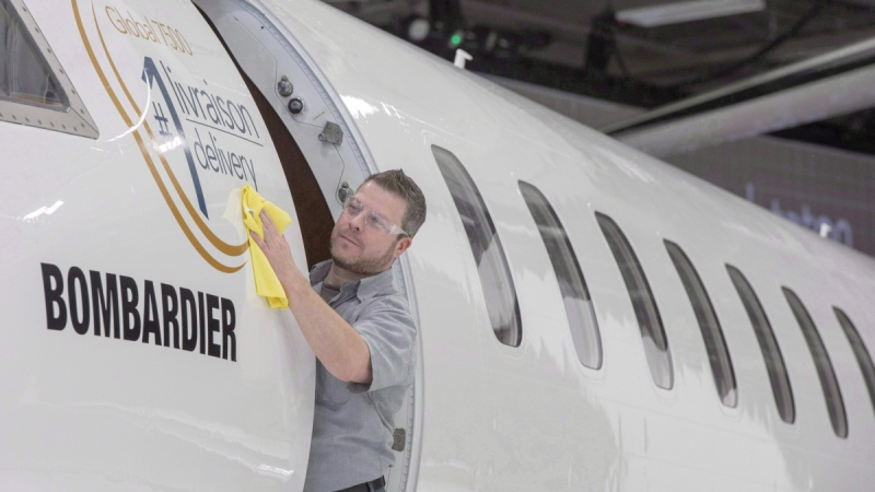 Francis Masse shines up Bombardier's new jetliner, the Global 7500, at the company's finishing plant in Montreal. (Ryan Remiorz / THE CANADIAN PRESS)