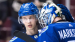 Vancouver Canucks' Elias Pettersson, left, and goalie Jacob Markstrom, both of Sweden, celebrate Vancouver's 5-1 winning NHL hockey game against the Philadelphia Flyers, in Vancouver on Dec. 15, 2018. THE CANADIAN PRESS/Darryl Dyck