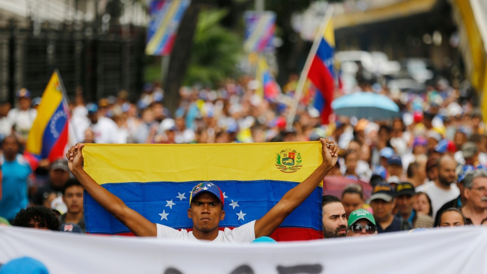 An opposition member holds a Venezuelan national flag during a protest march against President Nicolas Maduro in Caracas, Venezuela, Wednesday, Jan. 23, 2019. (AP / Fernando Llano)