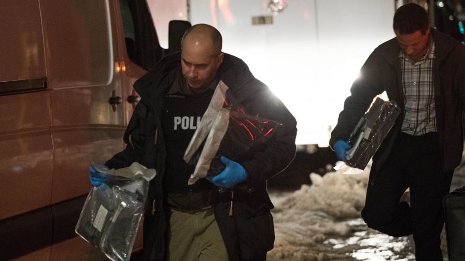 Police officers carry evidence after raiding a house in Kingston, Ontario, on Thursday Jan. 24, 2019. (THE CANADIAN PRESS/Lars Hagberg)