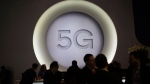 People stand next to a 5G logo during the Mobile World Congress wireless show, in Barcelona, Spain, on Feb. 28, 2018. (Francisco Seco / AP)