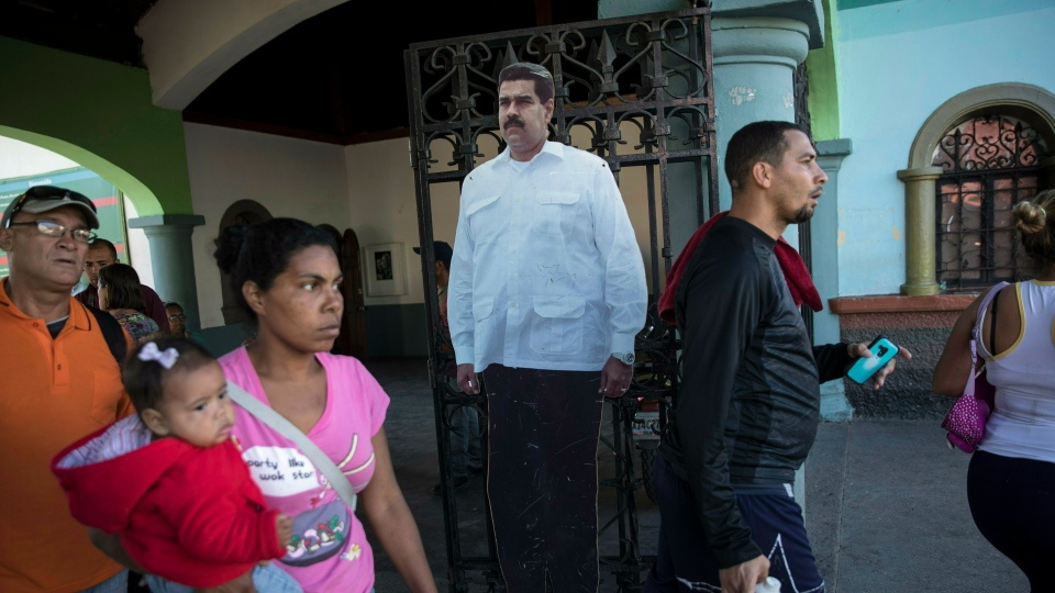 A cardboard life-size cut out of Venezuelan President Nicolas Maduro stands at the entrance of a public park in Caracas, Venezuela, Friday, Jan. 25, 2019. (AP Photo/Rodrigo Abd)